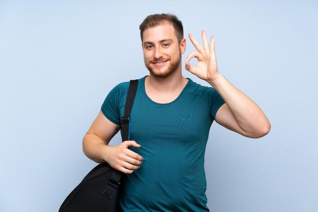 Blonder sportmann über der blauen wand, die okayzeichen mit den fingern zeigt
