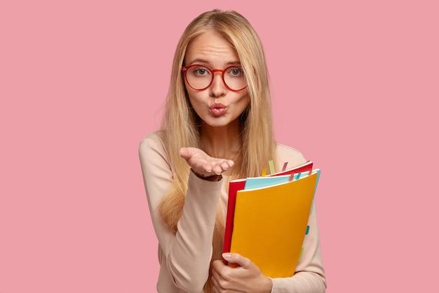 Blonder student, der gegen die rosa wand aufwirft