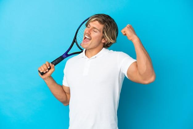 Blonder tennisspielermann lokalisiert auf blau, der einen sieg feiert