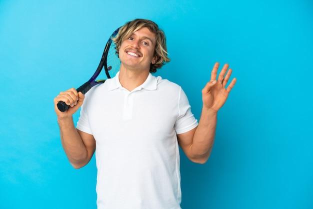 Blonder tennisspielermann lokalisierte das salutieren mit der hand mit glücklichem ausdruck