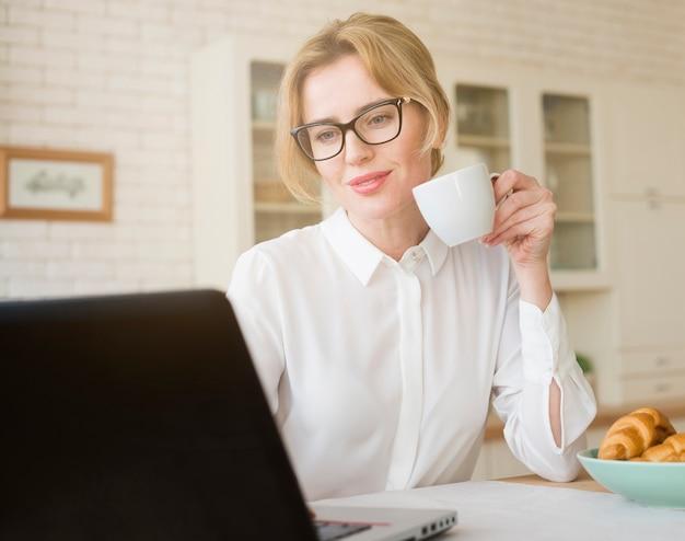 Blonder trinkender kaffee der geschäftsfrau bei der anwendung des laptops
