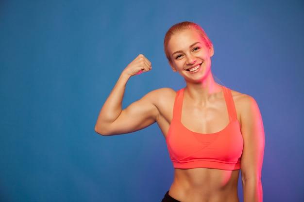 Blonder weiblicher athlet, der bizeps auf blauem hintergrund zeigt,