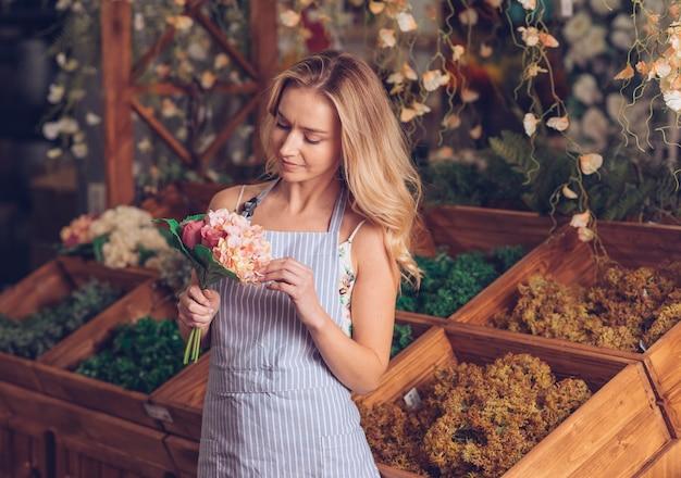 Blonder weiblicher florist, der den blumenstrauß steht vor hölzerner kiste betrachtet
