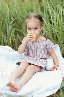 Blondes 3-jähriges schönes mädchen in einem braunen kleid auf einem weizenfeld mit einem krug milch, dorfleben.
