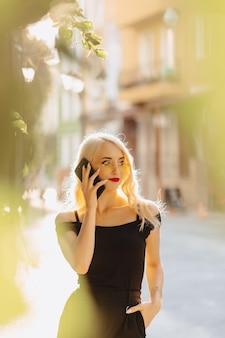 Blondes attraktives mädchen in der sonnenbrille mit telefon im warmen sommersonnenschein