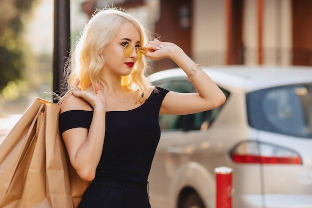 Blondes attraktives mädchen in der sonnenbrille nach dem einkauf im sommersonnenschein