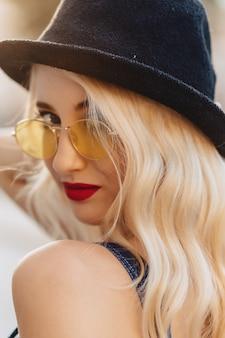 Blondes attraktives mädchen in der sonnenbrille und im stilvollen hut am sommersonnenschein städtisch
