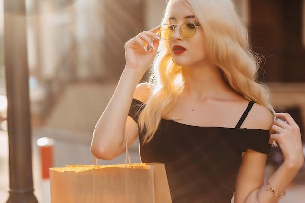 Blondes attraktives mädchen nach dem einkauf im sommersonnenschein