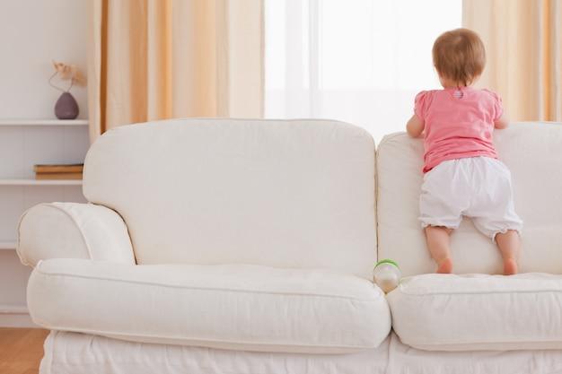 Blondes baby, das auf einem sofa steht