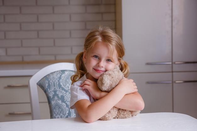 Blondes baby mit bärenspielzeug in der küche vor schlafenszeit