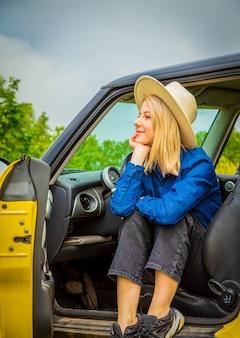 Blondes cowgirl im hut, der in einem auto auf dem land sitzt