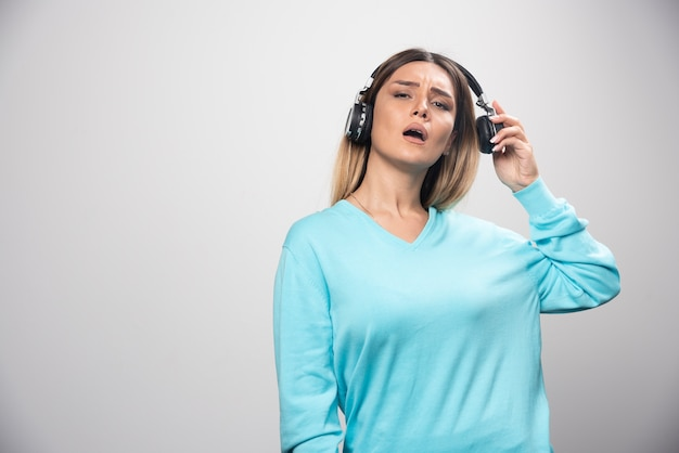Blondes dj-mädchen hört die musik über kopfhörer und mag es nicht