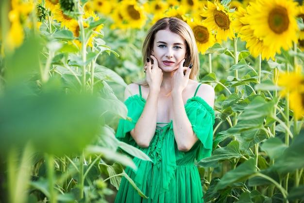 Blondes europäisches mädchen in einem grünen kleid auf natur mit sonnenblumen