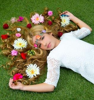 Blondes frühlingsmädchen mit blumen auf haar über gras