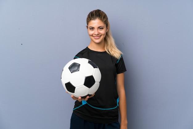 Blondes fußballspieler-jugendlichmädchen über grauer wand