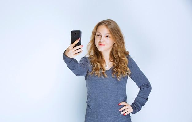 Blondes gelocktes mädchen, das ihr selfie nimmt. Kostenlose Fotos