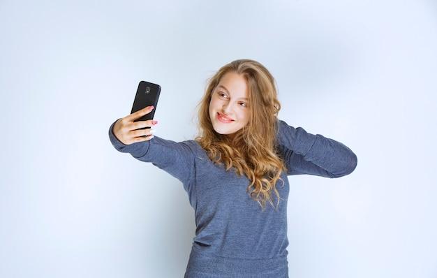 Blondes gelocktes mädchen, das ihr selfie nimmt.