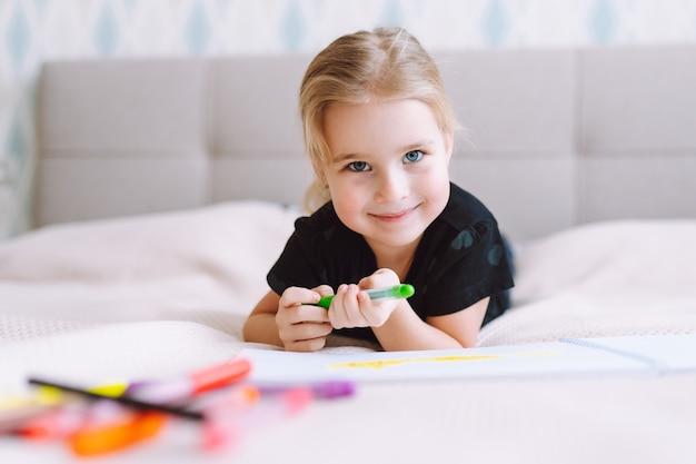 Blondes glückliches kleines mädchen, das mit bunten bleistiften zeichnet und schreibt, die zu hause auf dem bett liegen und vorschulerziehung, frühes lernen