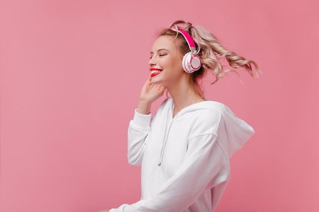 Blondes haar bewegt sich während aktiver tänze mit lustigen liedern