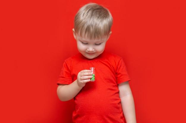 Blondes haar des kleinen jungen wird viele tablettenpillen in seinen händen essen