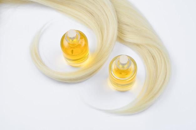 Blondes haar und ölflaschen isoliert auf weißem hintergrund.