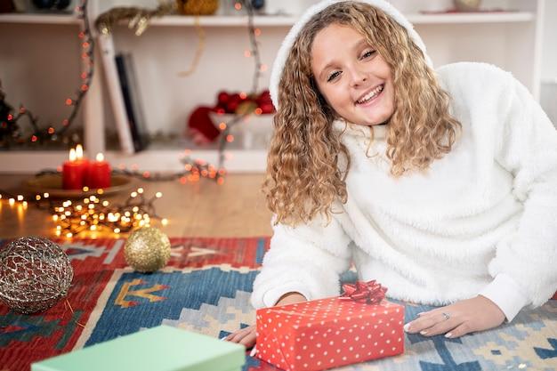 Blondes junges mädchen glücklich mit weihnachtsgeschenk