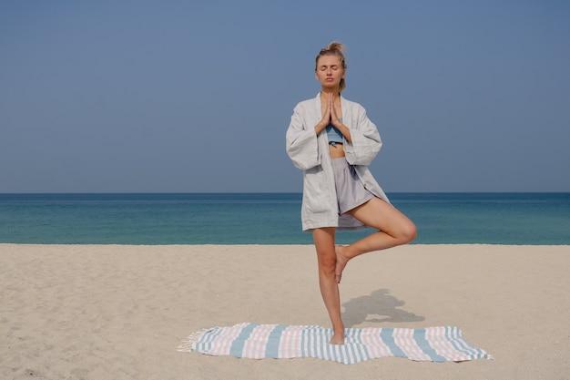 Blondes junges mädchen praktiziert yoga und meditation in der vrikshasana und baumhaltung asana am strand an einem sonnigen tag.