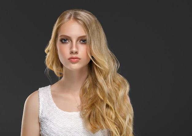 Blondes junges modell des lockigen langen haares. schönheitsmädchen mit lockiger perfekter frisur. studioaufnahme.