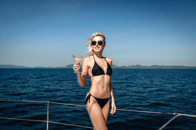 Blondes junges weibliches modell, das einen bikini und eine sonnenbrille trägt, die auf ihrem boot aufwerfen und ein glas mit einem cocktail halten.