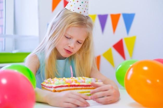 Blondes kaukasisches mädchen lächelt träumerisch und betrachtet geburtstagsregenbogenkuchen. festlicher bunter hintergrund mit ballonen. birhday party und wunschkonzept