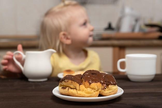 Blondes kind, das in der küche frühstückt. vanillepuddingkuchen auf kinderhintergrund. teetrinken in der küche.