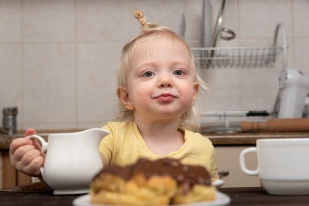 Blondes kind frühstückt in der küche. kind trinkt tee. kleines mädchen, das tee mit süßigkeiten trinkt.