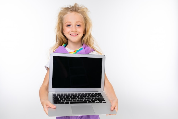 Blondes kind in einem lässigen blick zeigt ein laptop-display mit einem modell an einer weißen wand