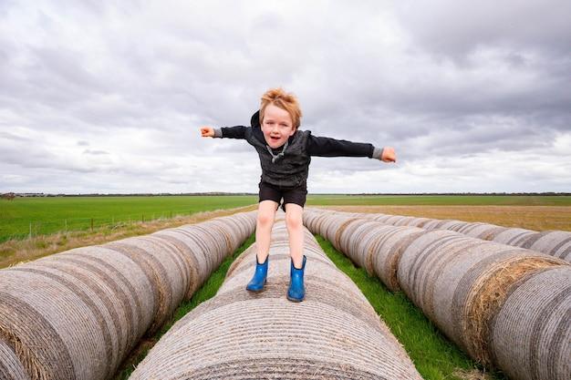 Blondes kind springt auf einer langen reihe runder heuballen am bewölkten tag - kindheit auf dem bauernhof