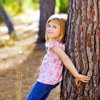 Blondes kindermädchen auf herbstbaumstamm