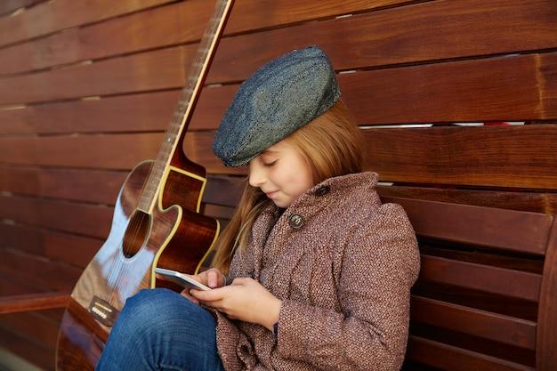 Blondes kindermädchen, das gitarre mit winterbarett spielt