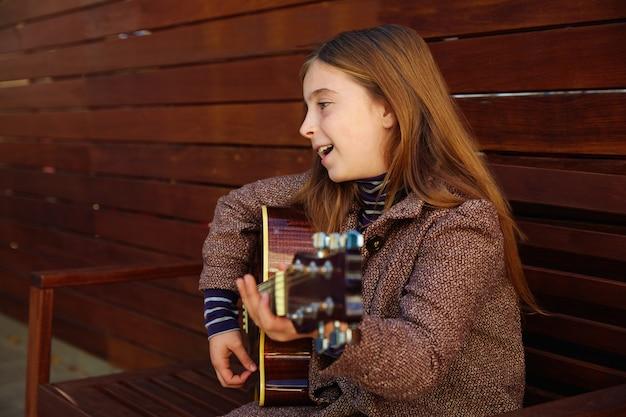 Blondes kindermädchen, das gitarre spielt