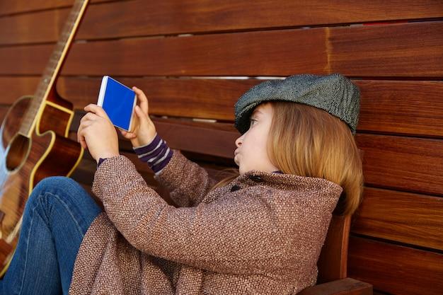 Blondes kindermädchen, das selfie gitarre und winterbarett nimmt