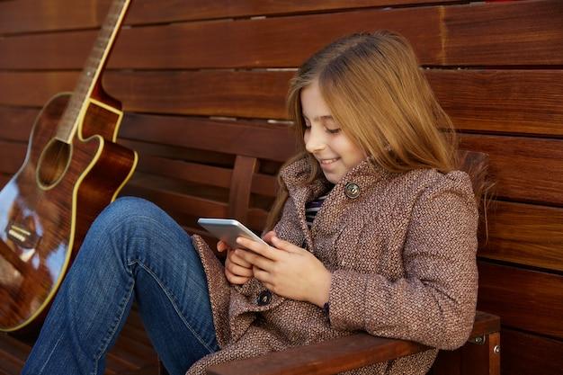Blondes kindermädchen, das smartphone spielt