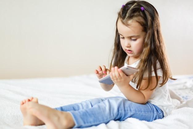 Blondes kindermädchen, das spaß mit beweglichem smartphone auf weißem sofa byod spielt