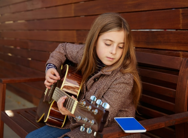 Blondes kindermädchen, das spielgitarre mit smartphone lernt