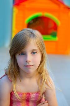 Blondes kindermädchen, das spielplatz im im freien lächelt