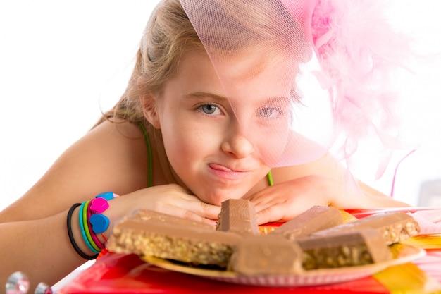 Blondes kindermädchen der hungrigen geste in den parteischokoladen