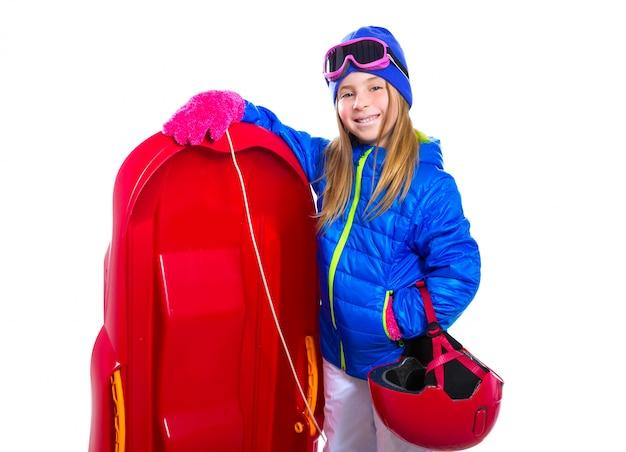 Blondes kindermädchen mit rotem schlittenschnee-ausrüstungssturzhelm und -schutzbrillen