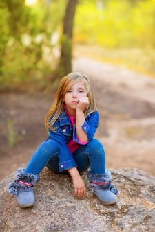 Blondes kindermädchen nachdenklich gelangweilt im wald im freien