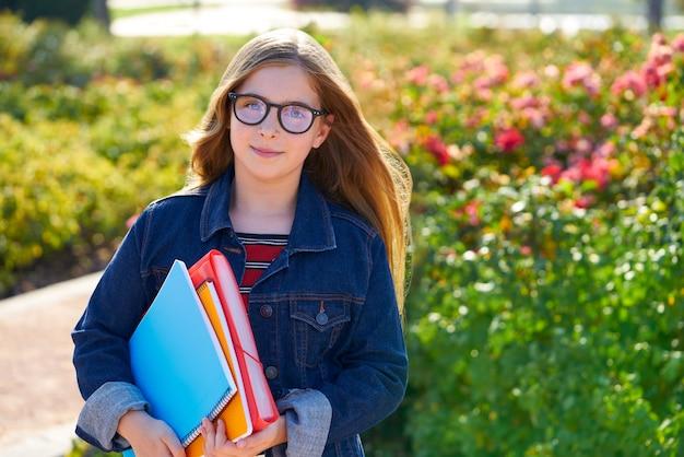 Blondes kinderstudentenmädchen im park mit gläsern