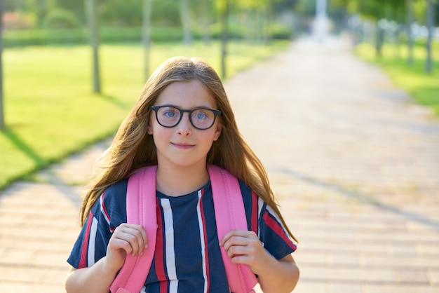 Blondes kinderstudentenmädchen mit gläsern im park