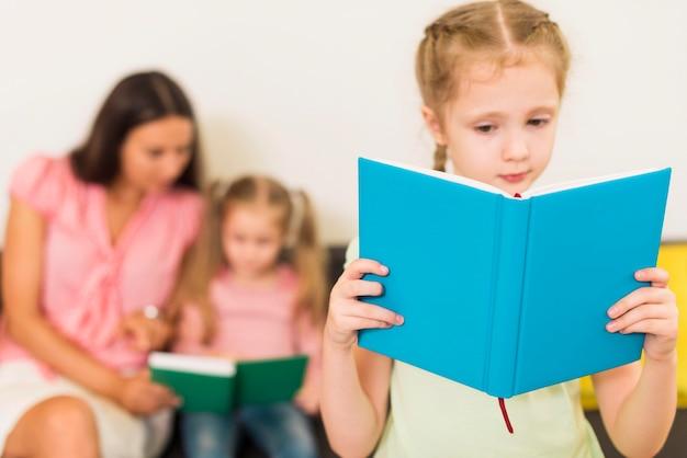 Blondes kleines kind, das von einem blauen buch liest