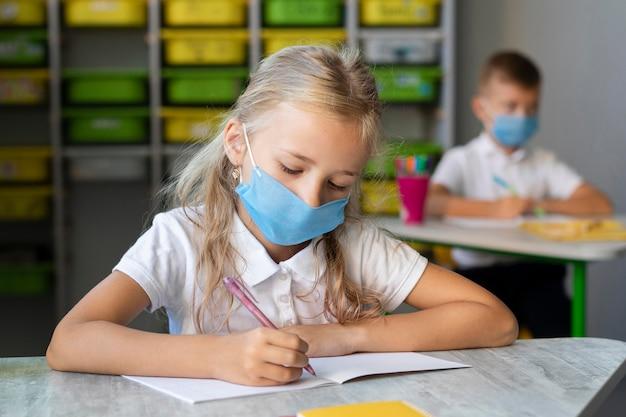 Blondes kleines mädchen, das beim tragen einer medizinischen maske schreibt