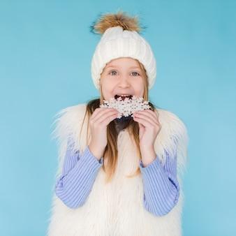 Blondes kleines mädchen, das eine schneeflocke isst